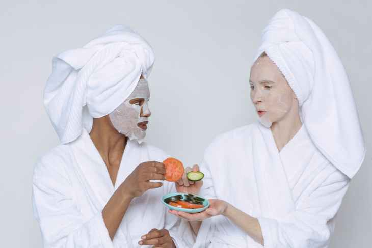 multiethnic women in sheet masks and towel with bathrobe having a pamper