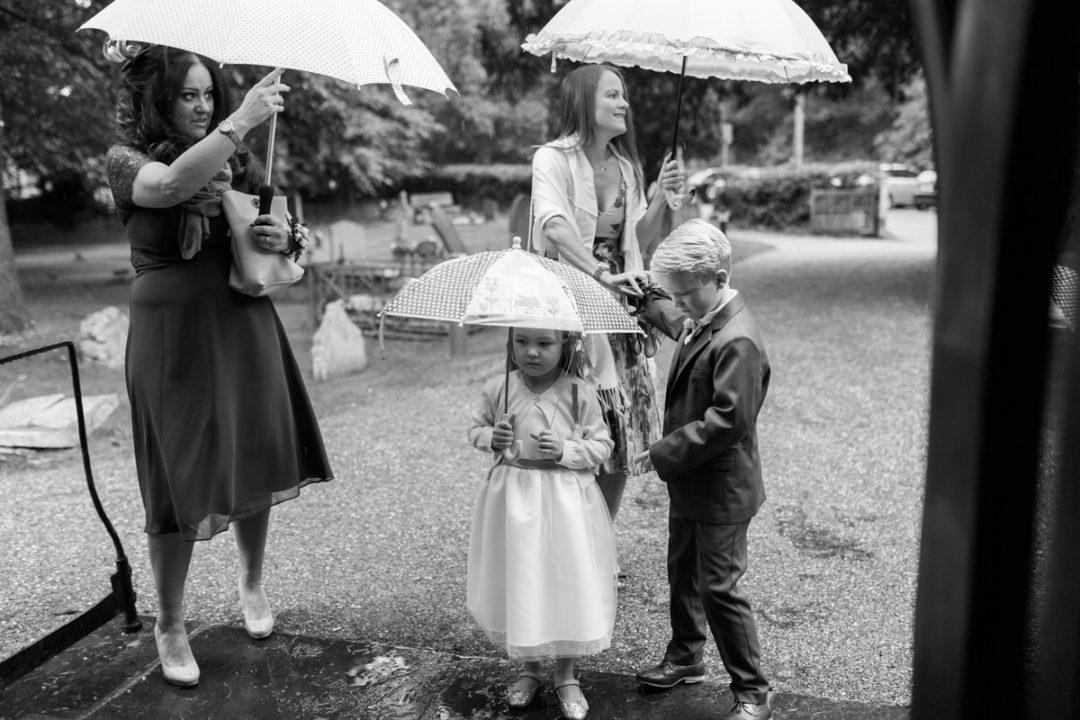 Rainy Essex wedding photos guests under umbrellas
