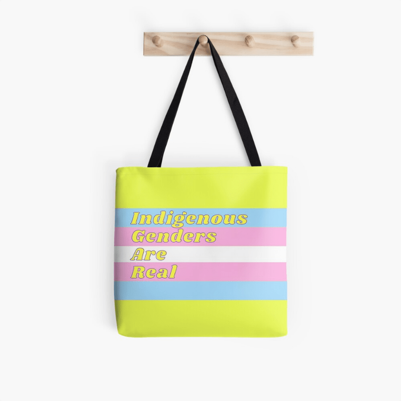 """A yellow tote bag with the trans flag colours printed on it, and """"Indigenous genders are real""""."""