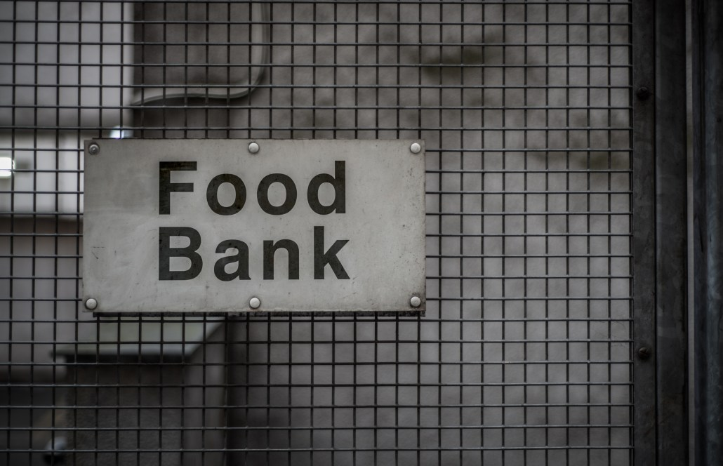 "Sign reading ""food bank"" on a metal fence"