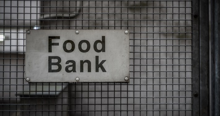 """Sign reading """"food bank"""" on a metal fence"""