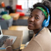 Black teenage girl wearing blue headphones, a brown shirt, and a green headband looks at the camera during a video call on a laptop.
