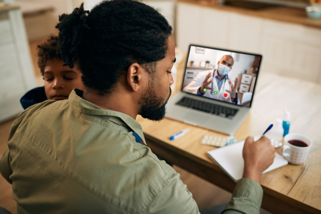 Black father having video call with pediatrician and writing notes while taking care of his sick son at home.