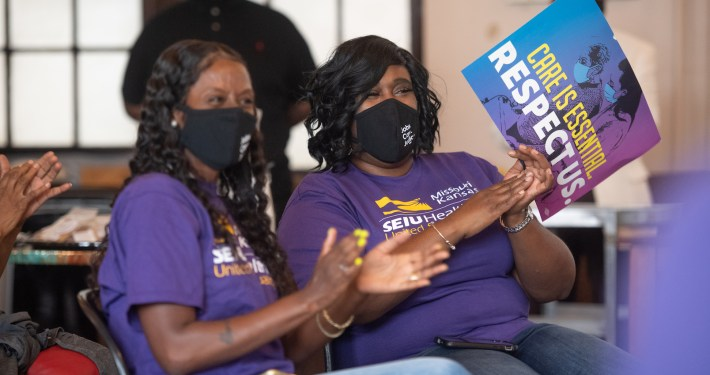 """Two Black women wearing purple SEI t-shirts and black masks are seated and clapping. One holds a sign reading """"Care is Essential, Respect Us"""""""