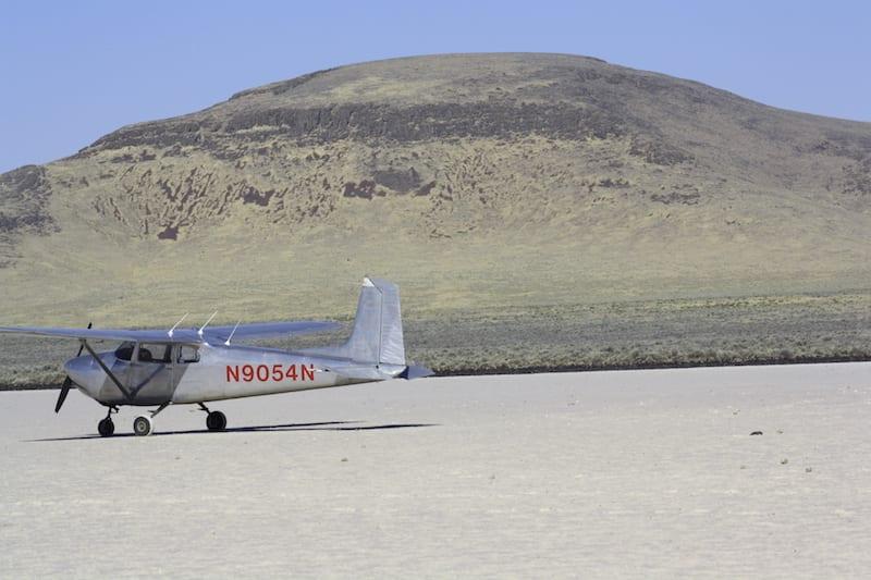Bob's plane by a dry lake bed.