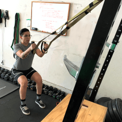 person performing a squat with the suspension trainer