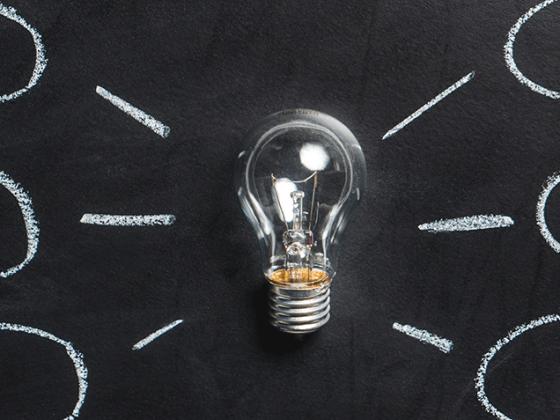Lightbulb against a chalkboard
