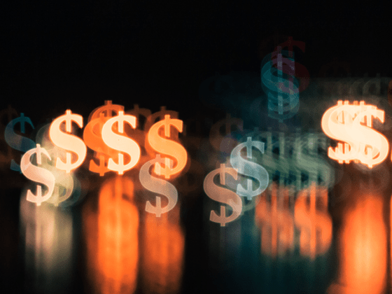 Neon dollar signs against a black background - pay transparency