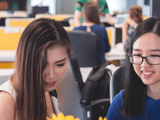 Two women in an office reviewing the first 5 things you should do a new job