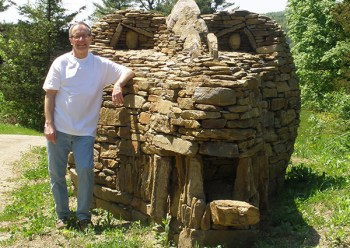 Raymond Hartman '69 stands beside his dry-laid stone dragon