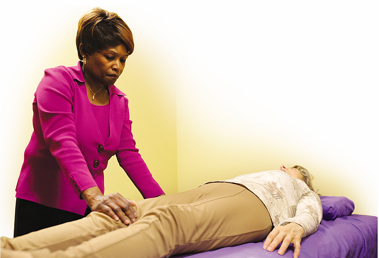 Denise Hollis, Healing Touch® Instructor and Practitioner treats a client