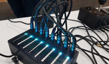 A joystick and eight cables plugged into a black box with blue lights.