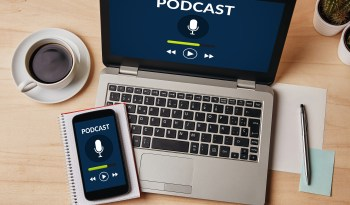 Podcast concept on laptop and smartphone screen over wooden table.