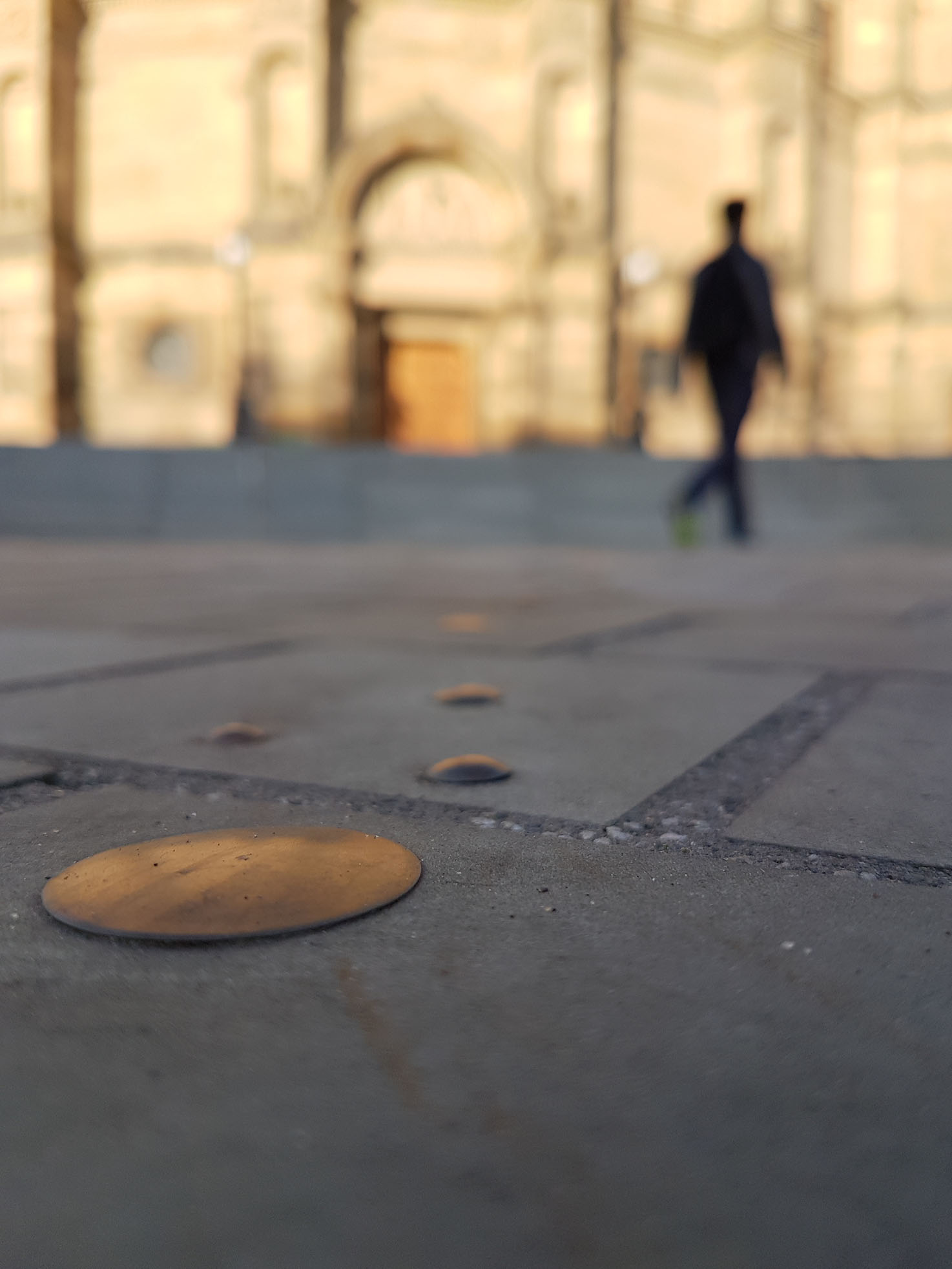 a close up of metal circles laind into an outdoor floor. In the background is a blurred silhouette of a person.