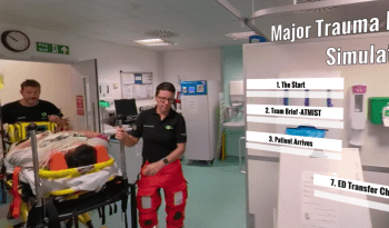 A screen shot of a video showing paramedics pushing a hospital trolley