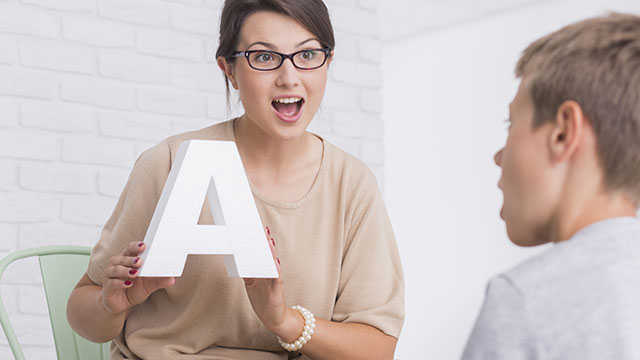 ABA Therapy with Therapist showing letter