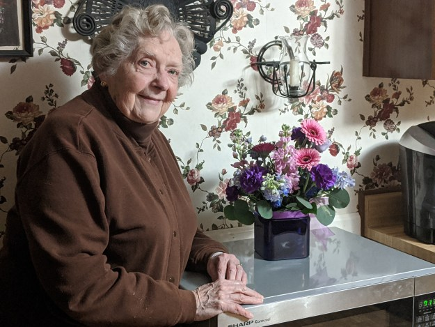 A senior citizen poses with a bouquet of flowers - How to Celebrate Memorial Day