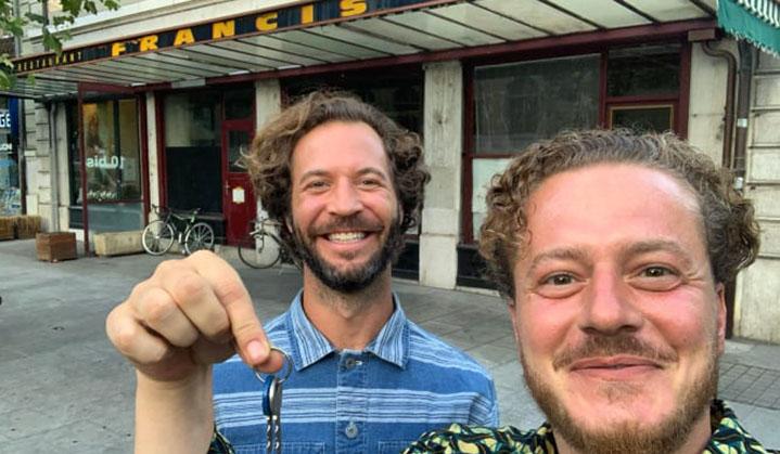 Deux jeunes hommes et une clé devant un restaurant