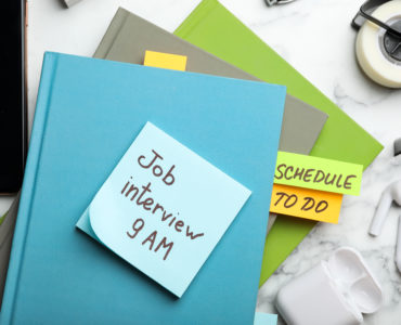 Reminder note about job interview and stationery on table, flat lay