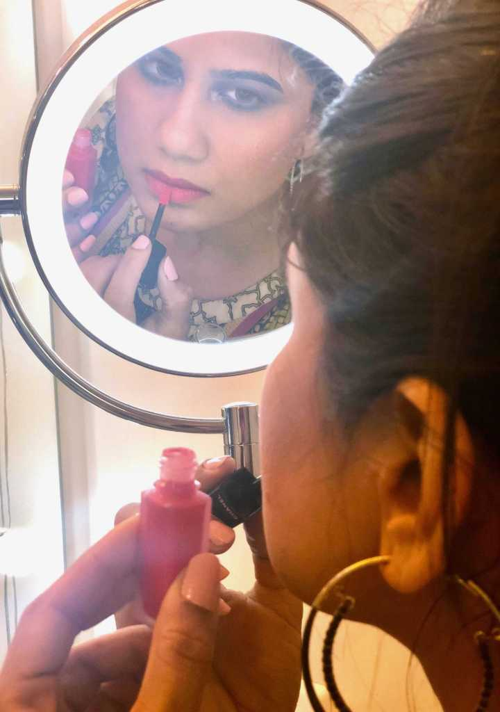 looking in mirror and applying Chanel Rouge Allure Ink shade Euphorie