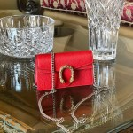Gucci Red mini leather Dionysus bag displaying on a glass table