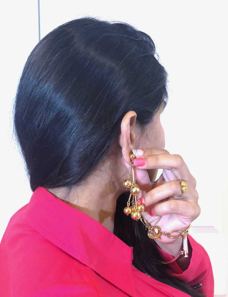 Showing her gold jewelry holding earring with her hand.