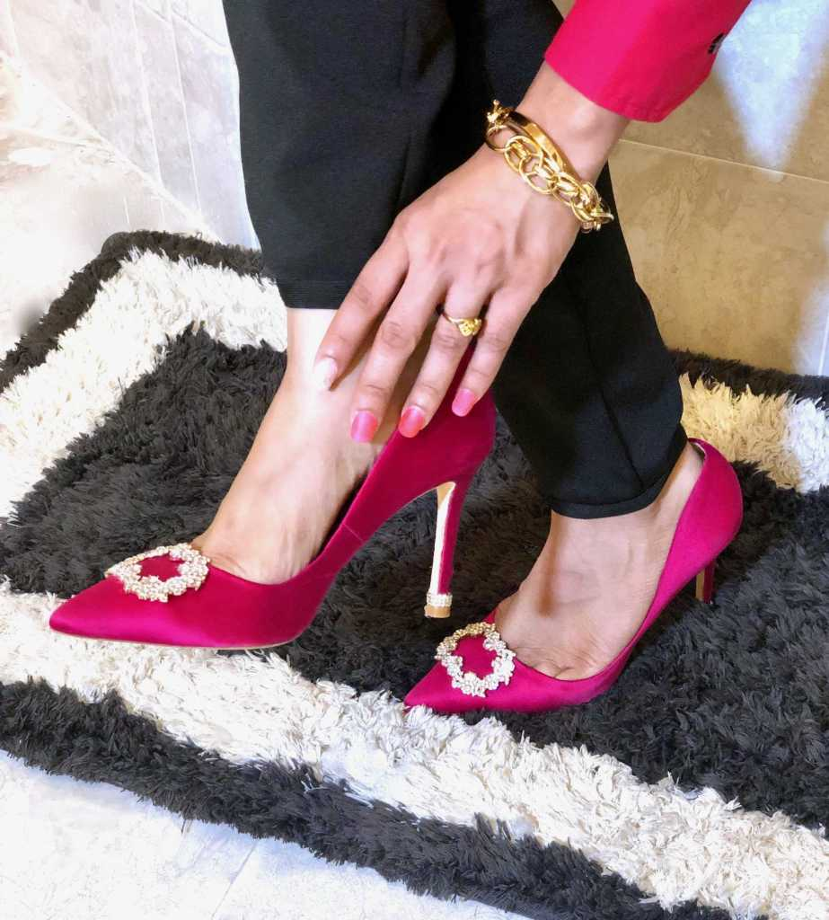 wearing beautiful pink pumps while holding foot with her hands.