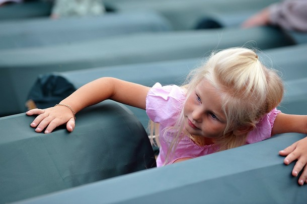 A Bosnian Muslim girl touches coffins of relatives, among coffins of Srebrenica victims displayed at the memorial centre of Potocari near Srebrenica on July 10, 2009. The 534 bodies were excavated from mass-graves in Eastern Bosnia and were identified as Muslims killed by Bosnian-Serb forces in the Srebrenica area. Bosnian Serb troops massacred up to 8,000 Bosnian Muslim men after capturing Srebrenica on July 11, 1995, during the 1992-1995 war in Bosnia-Herzegovina. The 534 identified victims will be buried on July 11 in the Potocari Memorial Center, next to some 3,500 victims of the massacre already buried there. AFP PHOTO ELVIS BARUKCIC (Photo credit should read ELVIS BARUKCIC/AFP/Getty Images)