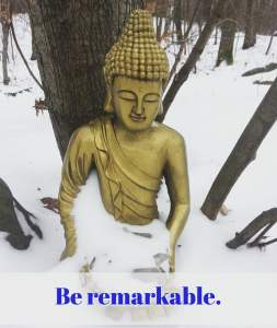 Statue of golden Buddha sitting in the snow with crystals in his lap