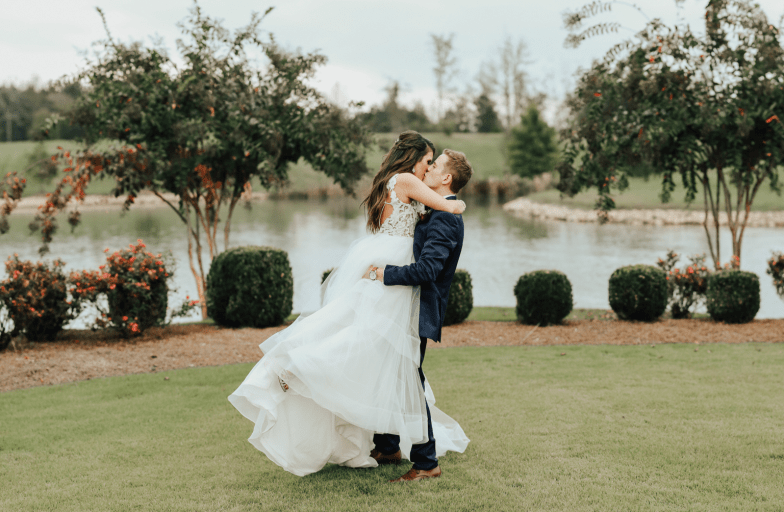 Bride and Groom in blue suit sharing a kiss.