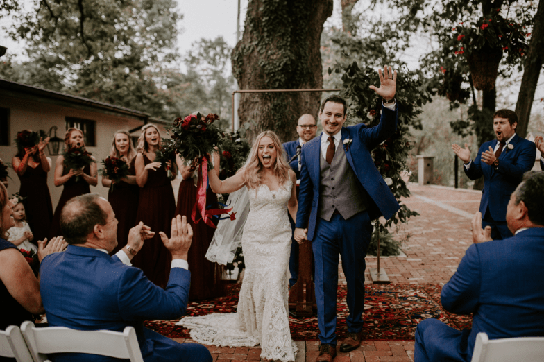 bohemian bride and groom in blue suit during processional