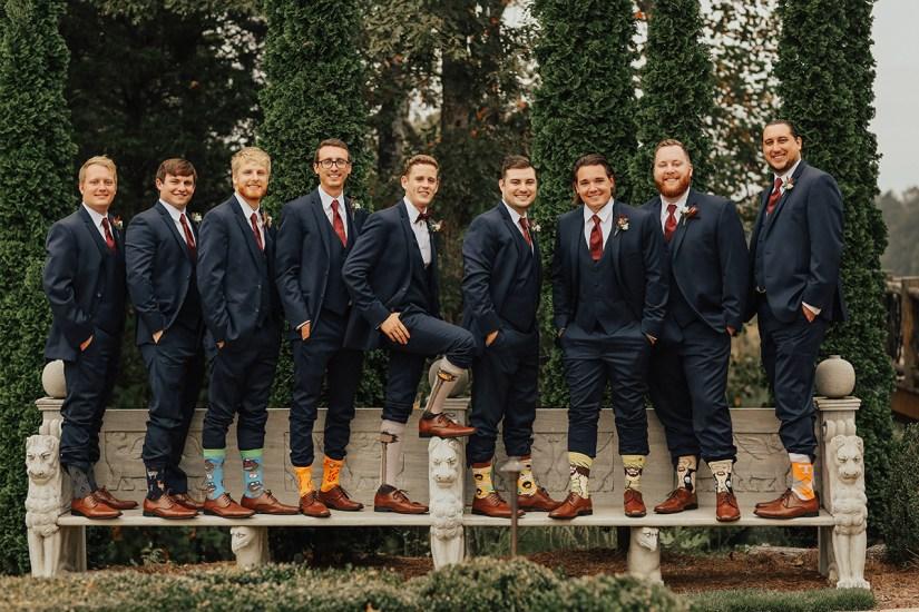 groom and groomsmen in blue suits showing off socks