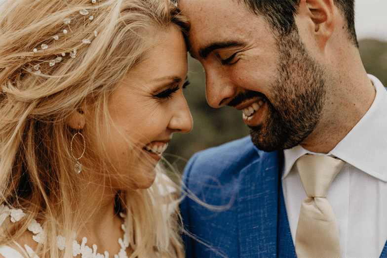 closeup of bride and groom in blue suit