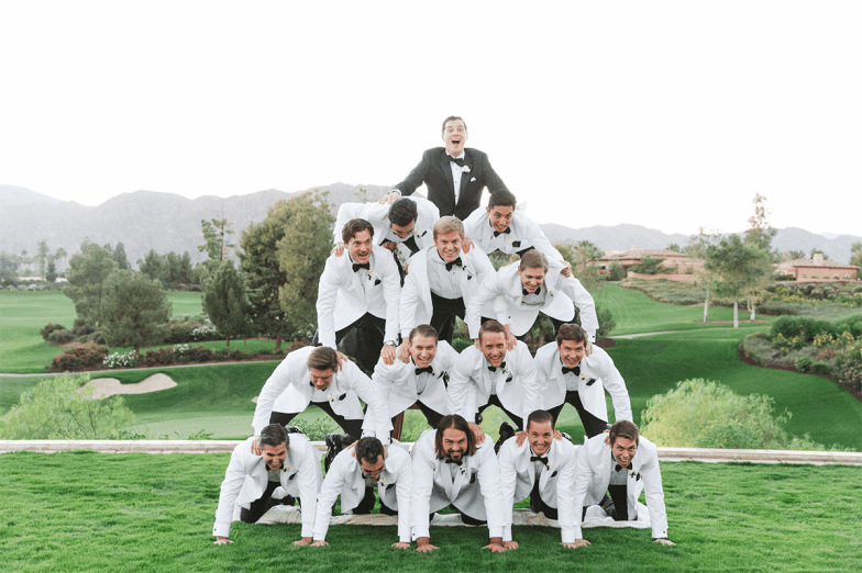 groom in black tuxedo on top of pyramid of groomsmen in white tuxedos