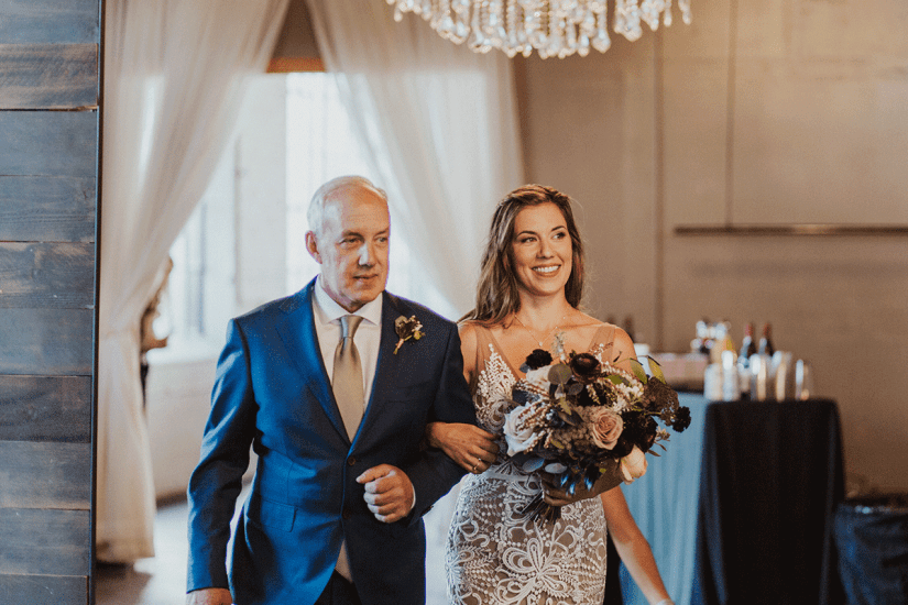 father of the bride in blue suit walking bride down the aisle