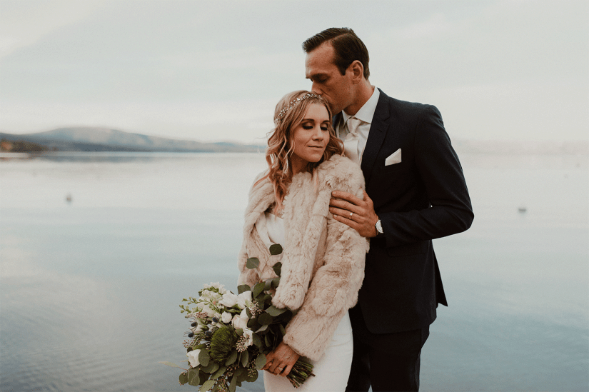 bride in fur coat with groom in navy suit