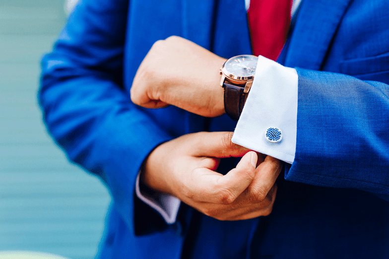 closeup of cufflinks and groom in blue suit