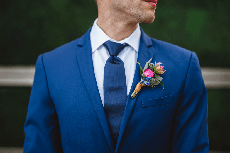 groom in blue suit with bright boutonniere