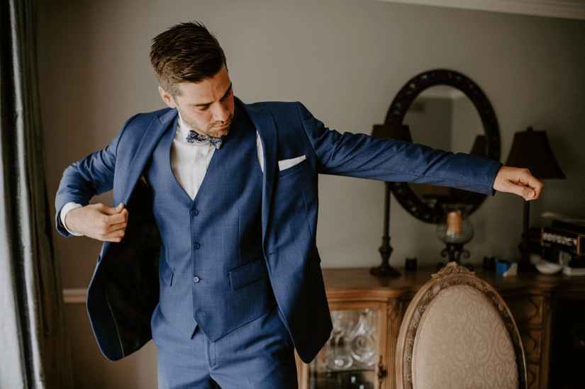 groom putting on blue suit jacket rental