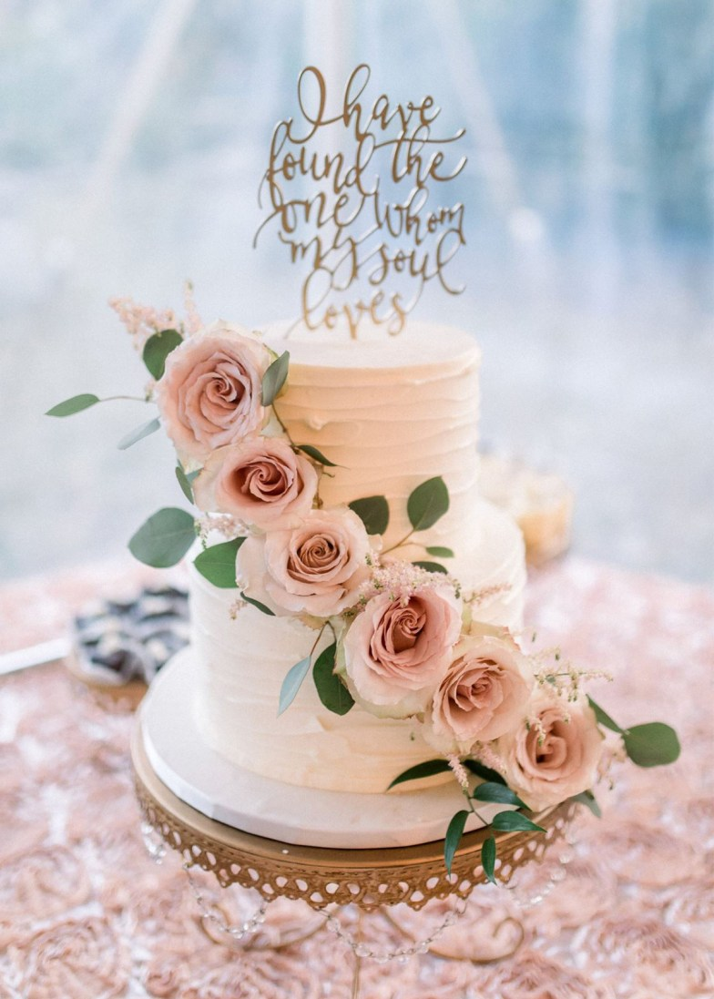 wedding cake with pink roses and word cake topper