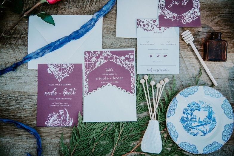 Wedding details shot invitation and paper suite burgundy