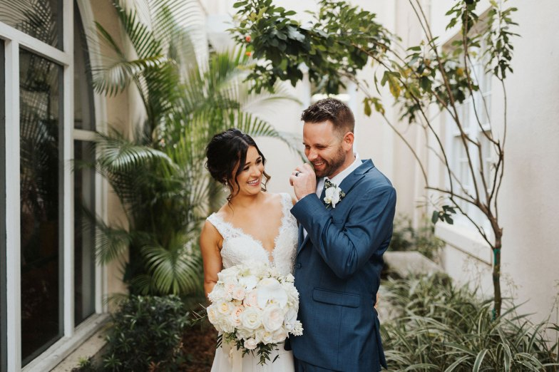 Bride and groom in blue suit laughing