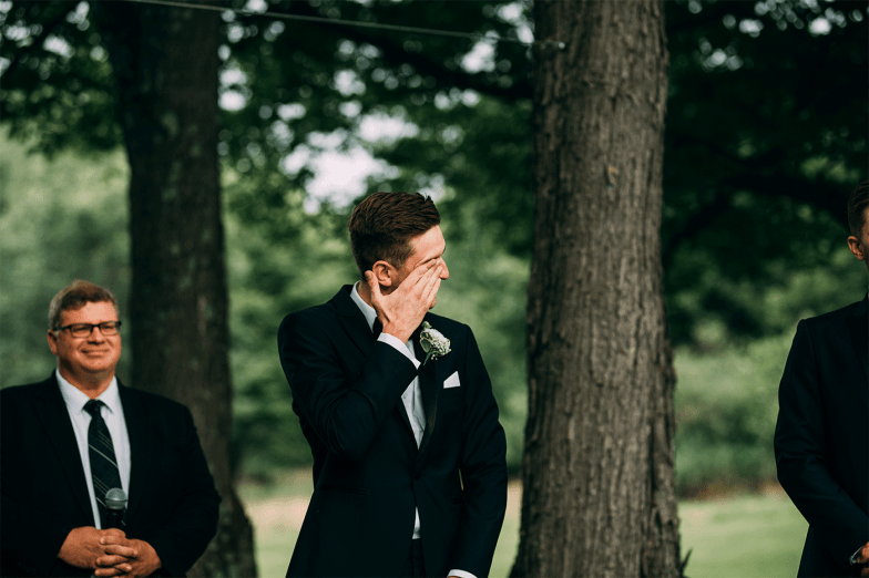 Groom in black tuxedo crying