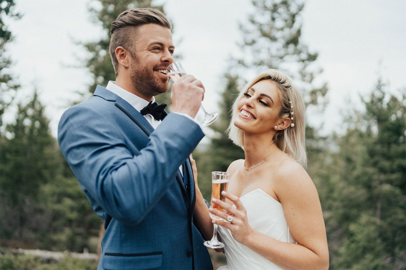 Groom in blue tuxedo and bride drinking champagne