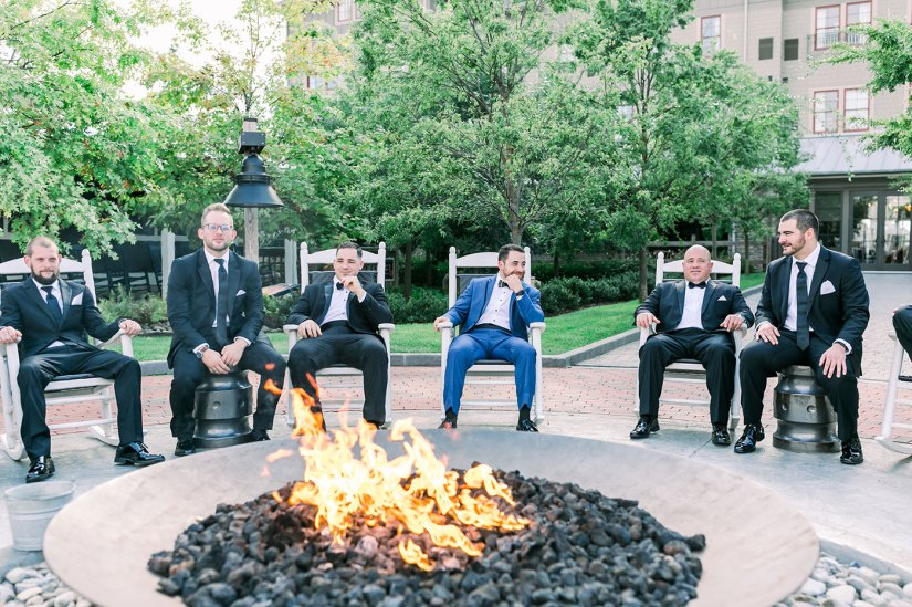 groom in blue suit and groomsmen in black suits sitting around a fire