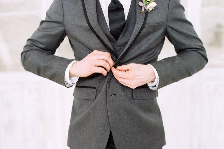 groom buttoning jacket of gray tuxedo