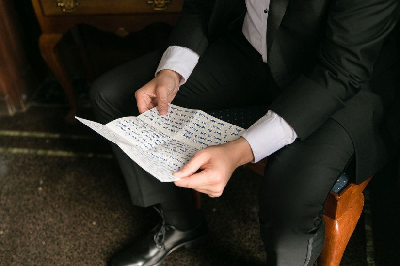 groom in black tuxedo reading letter from bride