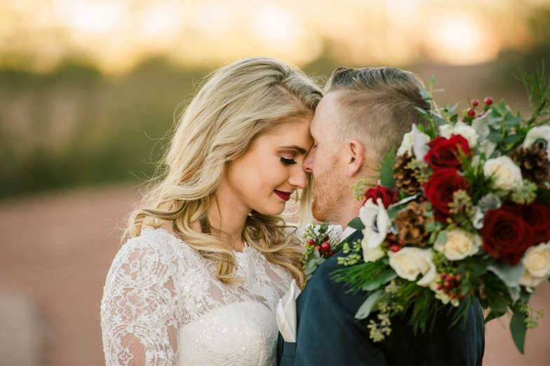bride and groom in blue suit with christmas boquet