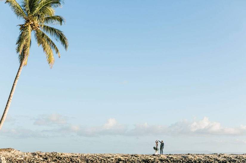 bride and groom walking on beach in hawaii