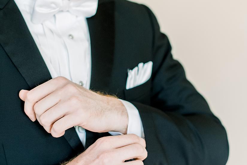 Man in Tuxedo fixing cufflink